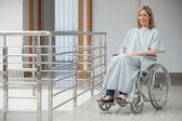 Lächelnde Frau sitzt im Rollstuhl im Krankenhaus-Korridor — Stockfoto