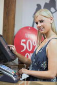 Woman is typing at the till while smiling — Stock Photo