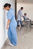 Distressed nurse standing against wall — Stock Photo