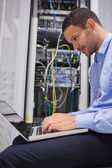 Man using laptop beside servers — Foto Stock