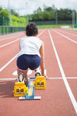 Woman at starting blocks on track — Stock fotografie