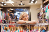 Girl leaning on a clothes rack — Stock Photo