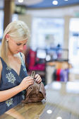 Woman standing at the counter while searching in her bag — Stock Photo