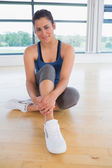 Happy woman sitting in fitness studio — Stock Photo