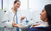 Doctor checking patients blood pressure — Stock Photo