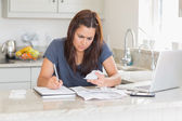 Woman calculating bills in the kitchen — Stock Photo
