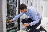 Man checking tablet pc as he is plugging cables into server — Stock Photo