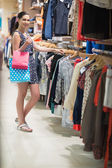 Woman standing at the clothes rack searching — Stock Photo