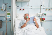 Patient lying in bed wearing oxegen mask — Stock Photo