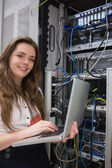 Woman happily using laptop to work on servers — Stock Photo