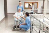 Two nurses looking after old women sitting in wheelchair — Stock Photo