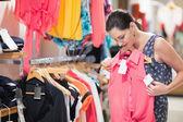 Woman looking at pink shirt — Stock Photo
