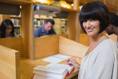 Black-haired woman reading a book in library — Stock Photo