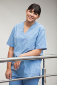 Nurse smiling while leaning against railing — Stock Photo
