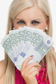Green eyed woman holding 100 euros banknotes — Stock Photo