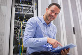 Happy technician working on tablet pc beside servers — Stock Photo
