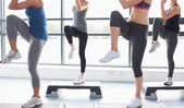 Women raising their legs while doing aerobics — Foto de Stock