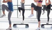 妇女在做有氧运动的同时提高他们的腿 — 图库照片