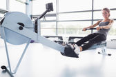 Smiling woman training on row machine — Stock Photo