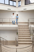 Nurse and doctor talking at top of stairwell — Stock Photo