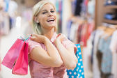 Woman laughing in clothes shop — Stock Photo