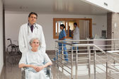 Doctor pushing woman in a wheelchair — Stock Photo