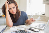 Young woman looking worried over finances — Stock Photo