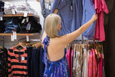 Woman looking through clothes — Stock Photo
