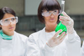 Female chemists viewing green liquid — Stock Photo