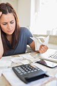 Brunette looking worried and holding bills — Stock Photo