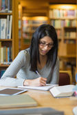 Woman doing some research in the library — Stockfoto