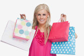 Smiling blonde showing shopping bags — Stock Photo