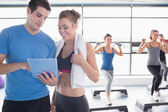 Trainer and woman talking while aerobics class lifiting weights — Stock Photo