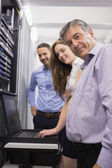 Three happy technicians checking servers with laptop — Stock Photo