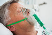Man in bed with oxygen mask — Stock Photo