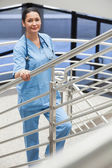 Smiling nurse in a stairwell leaning on the railings — Stock Photo
