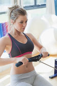 Woman pulling on row machine — Stock Photo