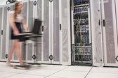 Woman pushing computer through data center — Stock Photo