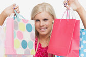 Beautiful blonde showing shopping bags — Stock Photo