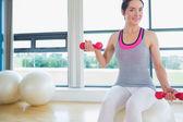 Glückliche frau lifitng gewichte auf gymnastikball — Stockfoto