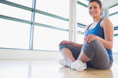 Woman sitting on floor and smiling — Stock Photo