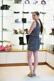 Woman standing at shoe display — Stock Photo