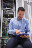 Technician using tablet pc to work on servers — Stockfoto