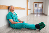 Doctor is sitting on the floor eyes closed — Stock Photo