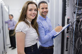 Two smiling technicians checking the servers — Stock Photo