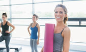 Woman holding a mat and two other women — Stock Photo