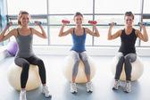 Oturan üç gülümseyen kadın egzersiz topları ve kaldırma ağırlığı — Stok fotoğraf