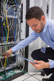 Man using tablet pc to work on servers — Stock Photo