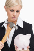 Sad businesswoman holding a hammer and a piggy-bank — Stock Photo
