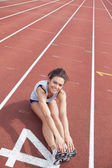 Female runner stretching her legs — Stockfoto